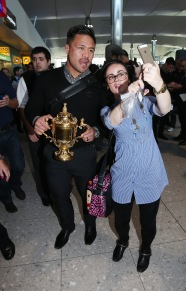 LONDON, ENGLAND - NOVEMBER 02: Keven Mealamu, of Rugby World Cup winners, the New Zealand All Blacks, poses with a supporter as he holds the Webb Ellis Cup as the team arrive at Heathrow Airport at the start of their journey back to New Zealand on November 2, 2015 in London, United Kingdom. (Photo by David Rogers/Getty Images for England 2015)